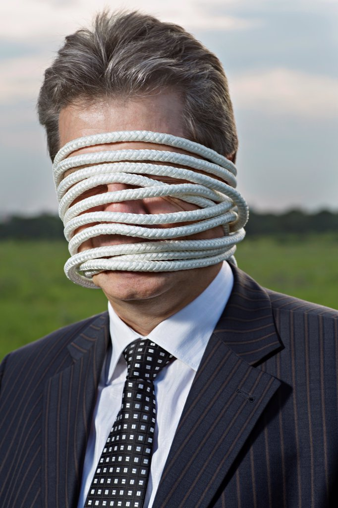 Stock Photo: 1570R-142785 A mature businessman with rope wrapped around his face