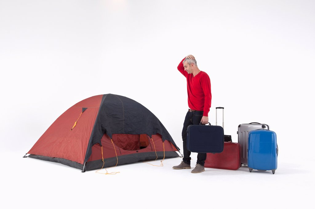 An unhappy man with loads of luggage looking at a tent with uncertainty : Stock Photo
