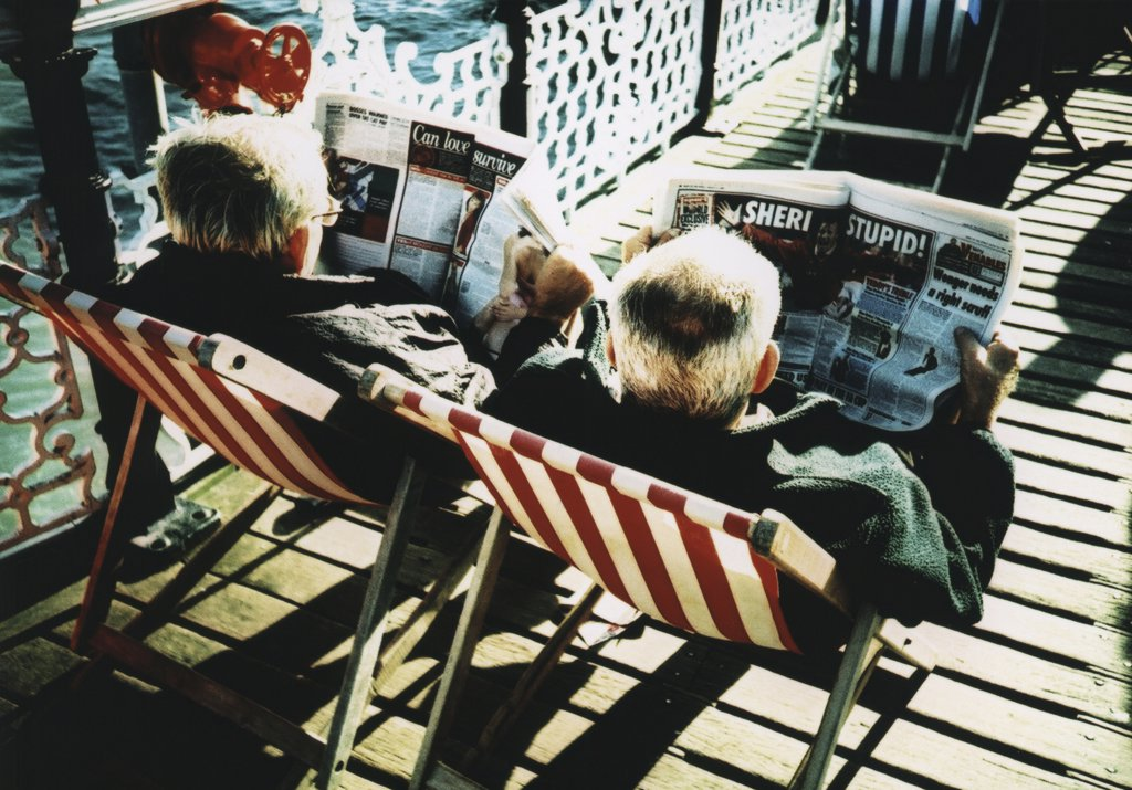 Stock Photo: 1570R-18029 two men sitting in beach chairs reading newspapers