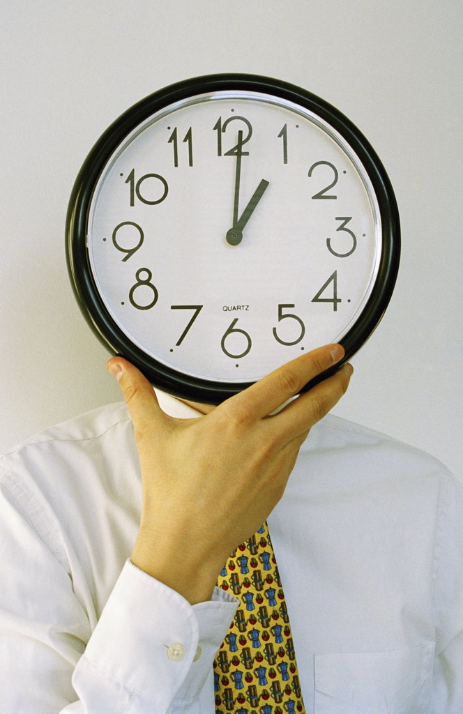 Stock Photo: 1570R-32025 A businessman holding a clock in front of his face