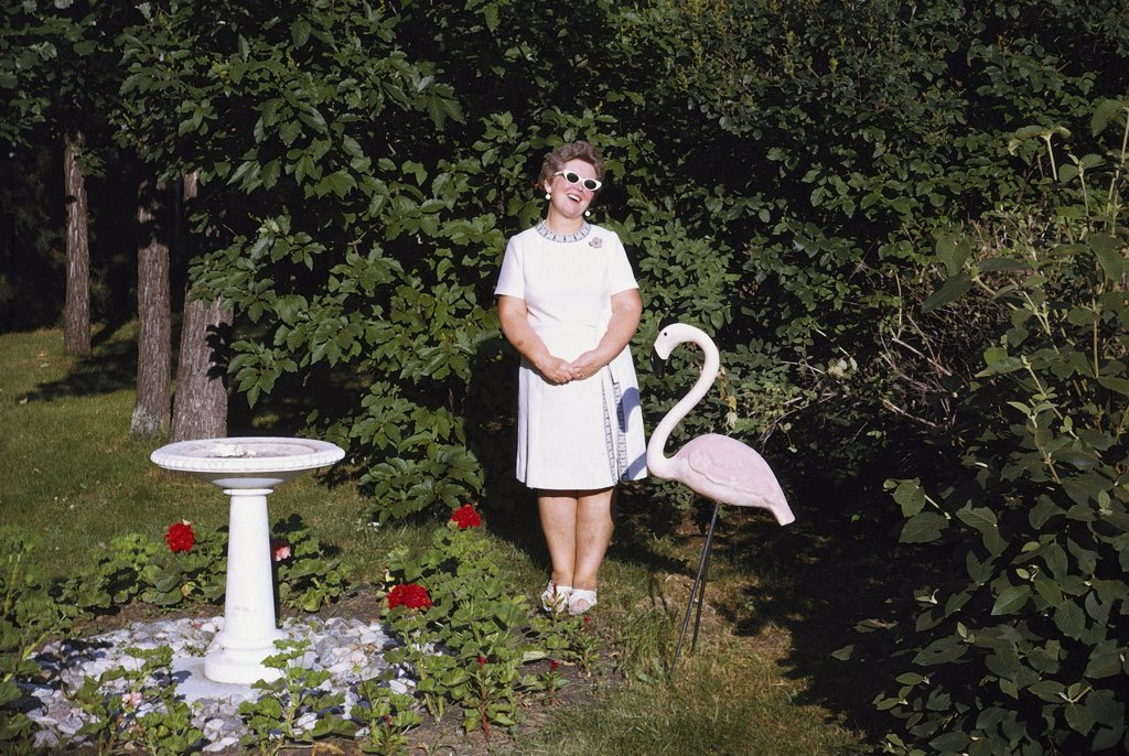 Stock Photo: 1570R-35003 A woman standing in a garden next to a statue of a pink flamingo