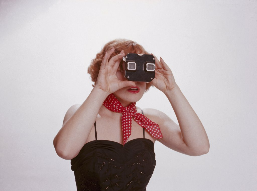 A 1950's woman with a red scarf looking through a slide viewer : Stock Photo