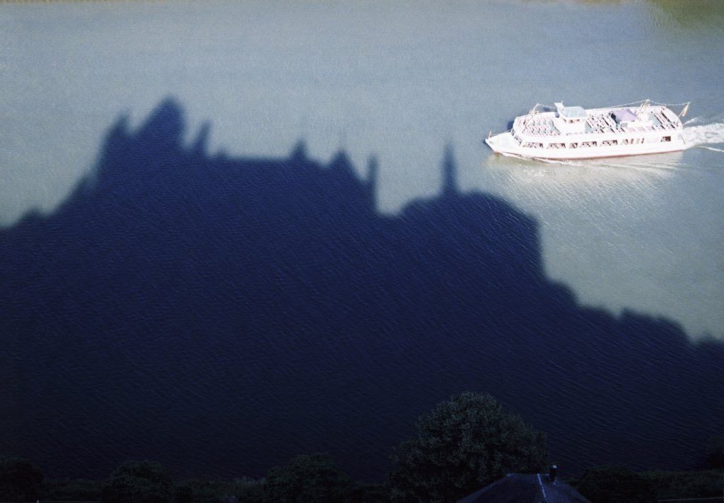 boat crossing the shadow of a castle : Stock Photo