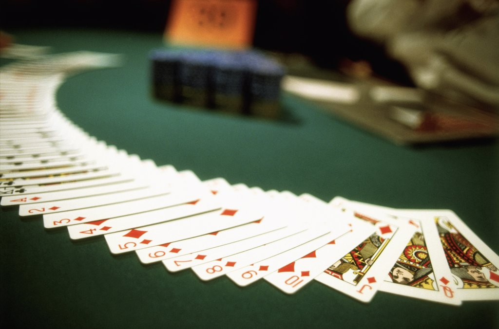 Playing cards spread out across a casino table : Stock Photo