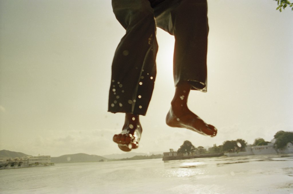 Stock Photo: 1570R-53024 A person's legs jumping into water