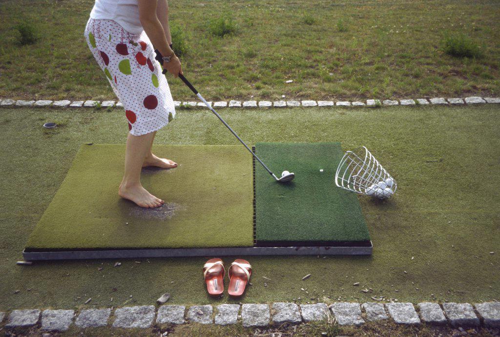 A woman hitting golf balls at a driving range : Stock Photo