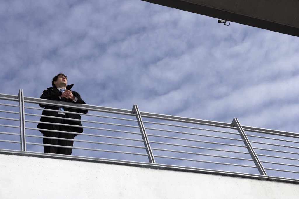 Stock Photo: 1570R-78004 A businessman leaning on a railing