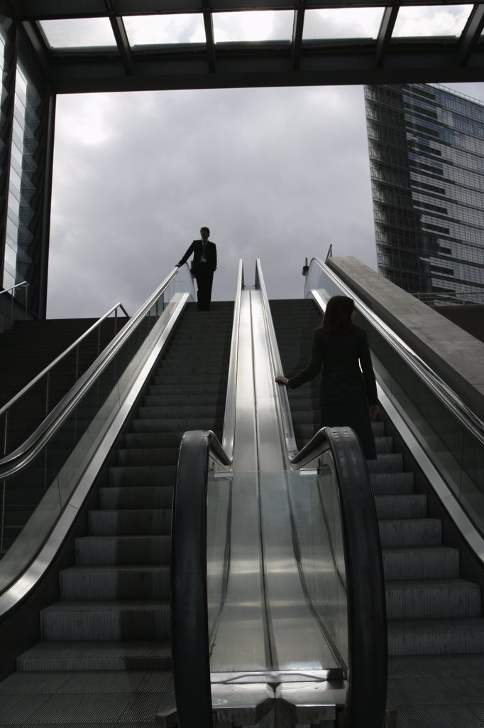 A businessman and a businesswoman riding an escalator : Stock Photo