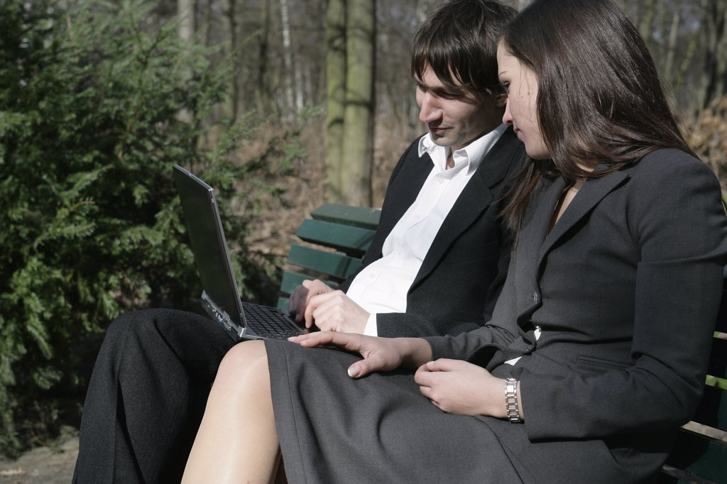 Stock Photo: 1570R-78037 A businessman and a businesswoman looking at a laptop computer on a park bench