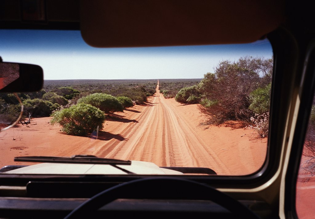 A view of a desert road in Australia through the windshield of an off-road vehicle : Stock Photo