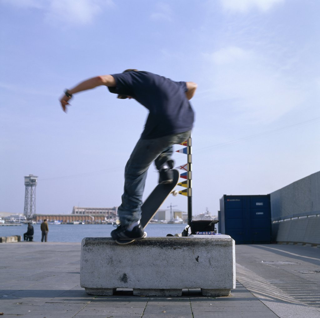 Man on skateboard balancing on stone block  : Stock Photo