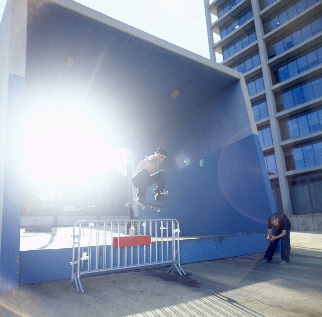 Man on skateboard jumping over barrier : Stock Photo