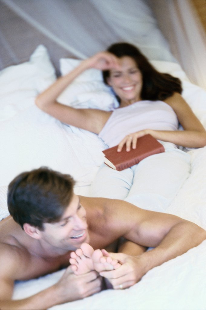 Young man massaging the feet of a young woman in bed : Stock Photo