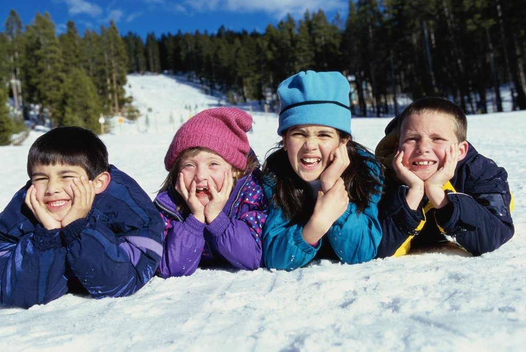 Portrait of a group of children lying in snow : Stock Photo