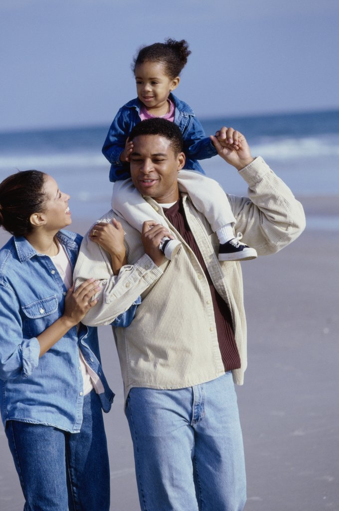 Parents smiling with their daughter on the beach : Stock Photo