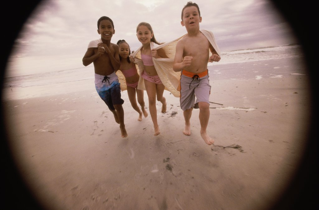 Portrait of two boys and two girls running on the beach : Stock Photo
