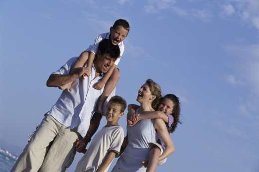 Stock Photo: 1574R-010643 Portrait of a mother and father on the beach with their three children