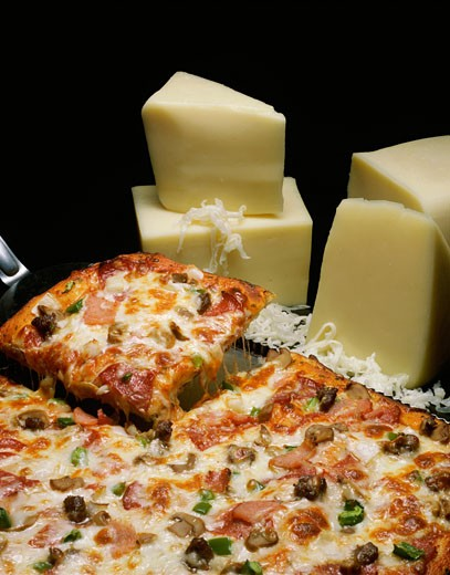 Wedges of cheese near a pizza : Stock Photo