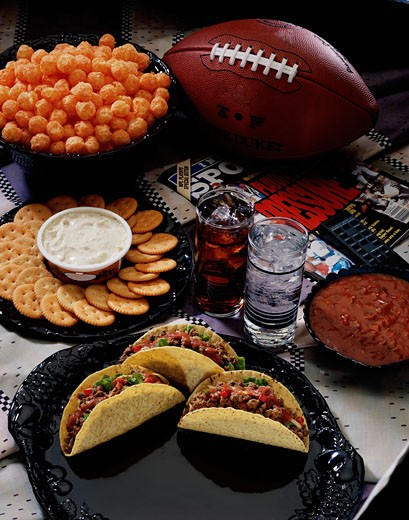 High angle view of crackers and dip near a plate of tacos : Stock Photo