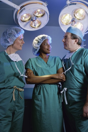 Stock Photo: 1574R-011639A Three surgeons standing in an operating room
