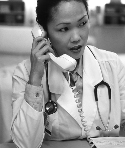 Female doctor talking on a telephone : Stock Photo