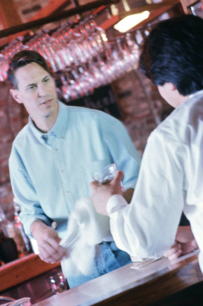 Stock Photo: 1574R-012169 Rear view of a young man and a bartender at a bar