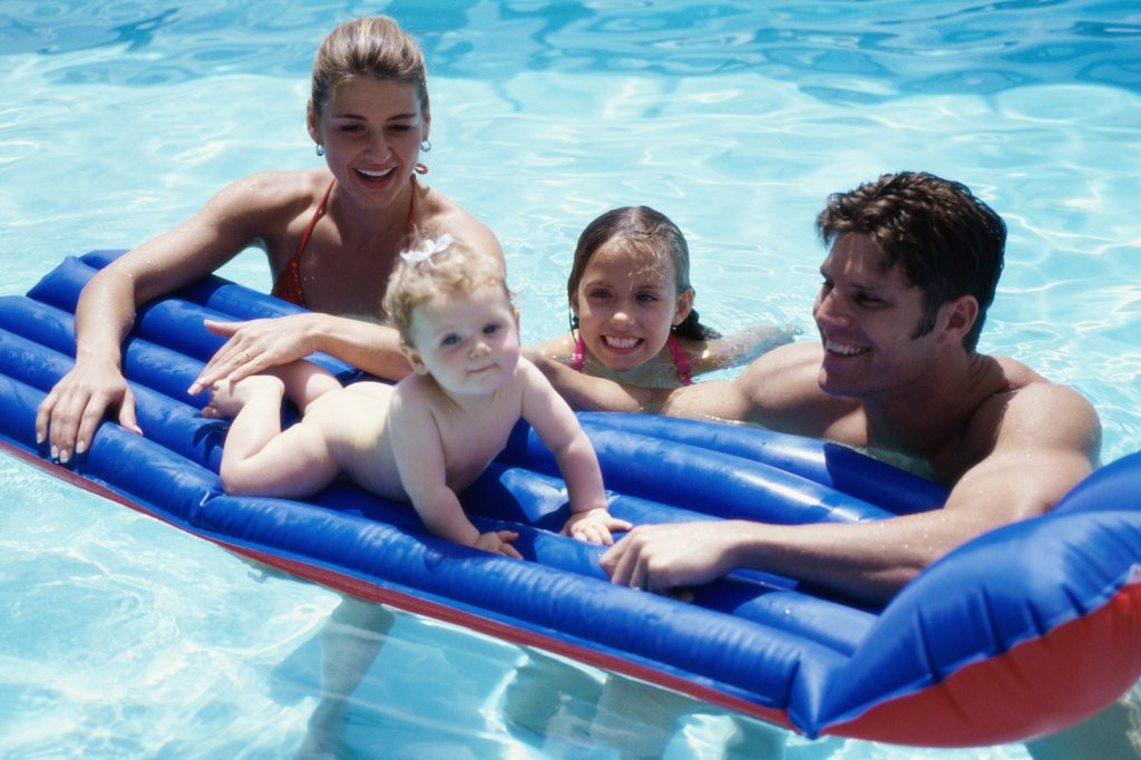 Parents and their two daughters in a swimming pool : Stock Photo