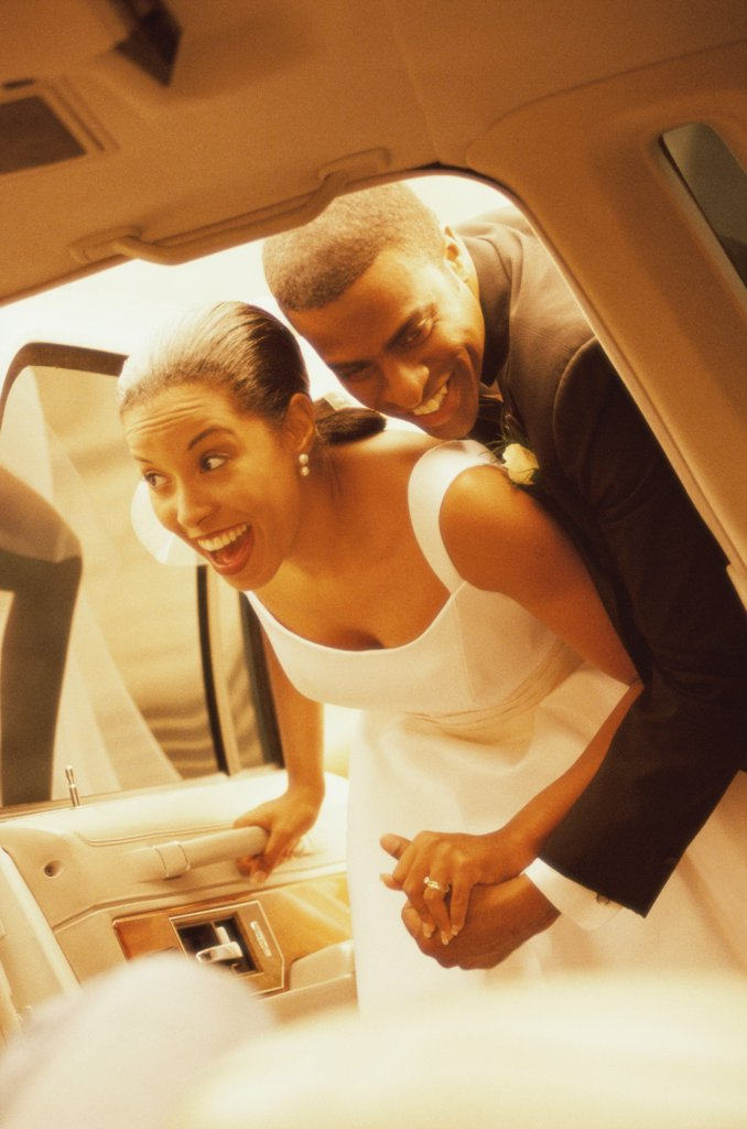 Stock Photo: 1574R-012378 Newlywed couple looking inside of a car