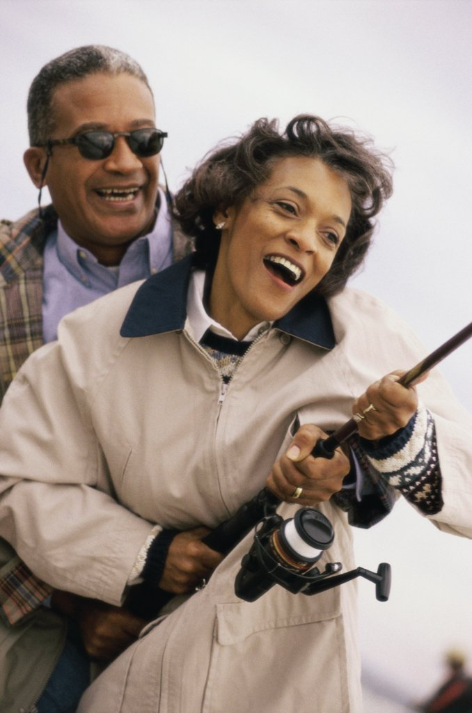 Close-up of a mature couple holding a fishing rod : Stock Photo