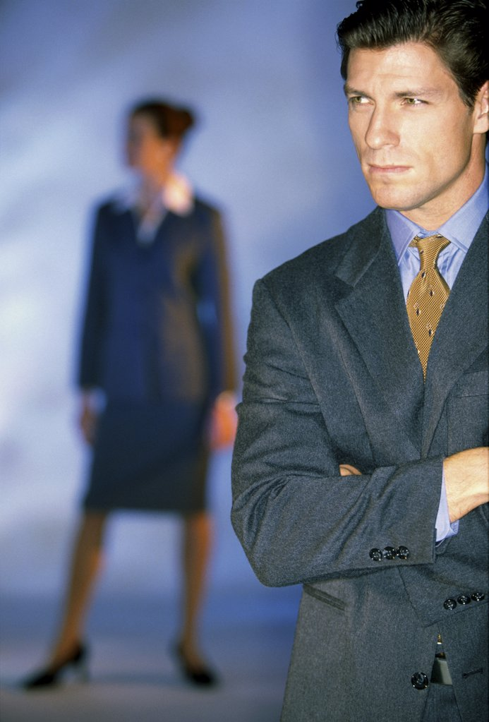Businessman standing with a businesswoman in the background : Stock Photo