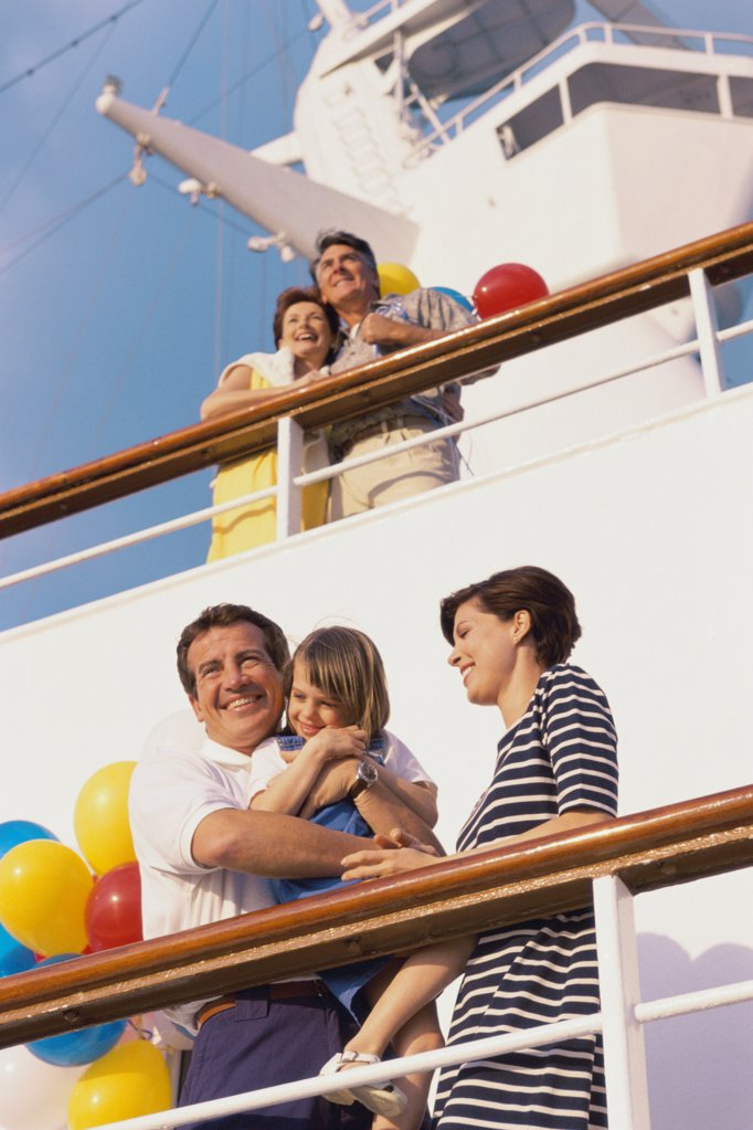 Low angle view of a mid adult couple with their daughter standing on the deck of a cruise ship smiling : Stock Photo