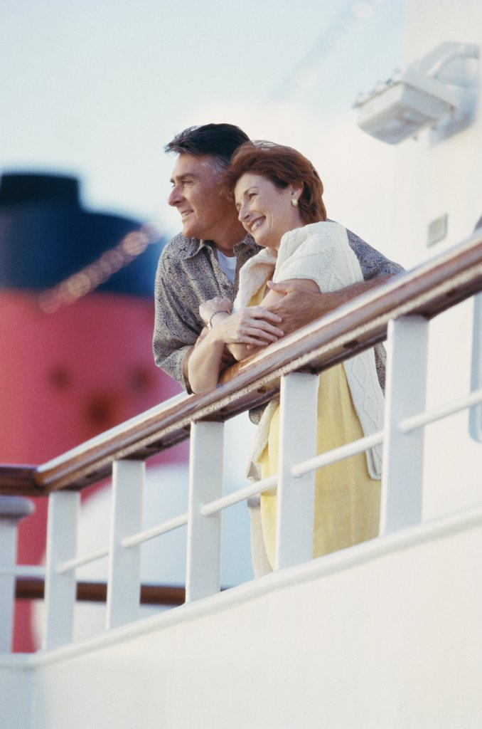Stock Photo: 1574R-012527A Low angle view of a mature couple standing on the deck of a cruise ship