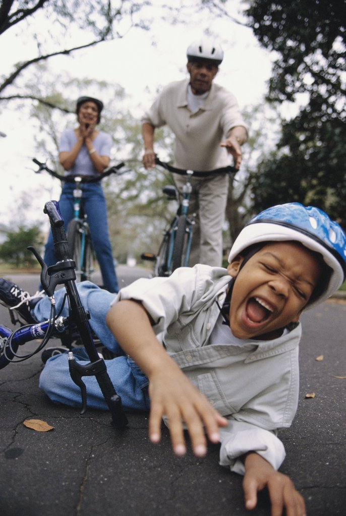 Stock Photo: 1574R-012582B Close-up of a boy fallen off of a bicycle with his grandparents standing behind him