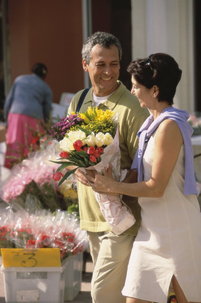 Side profile of a mid adult couple holding a bouquet of flowers : Stock Photo