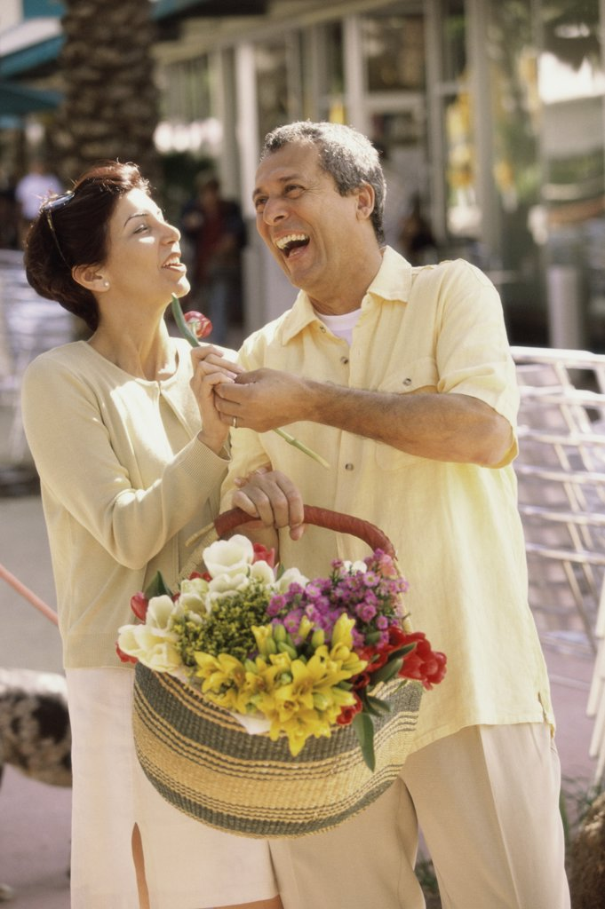 Mature man giving a flower to a mature woman : Stock Photo