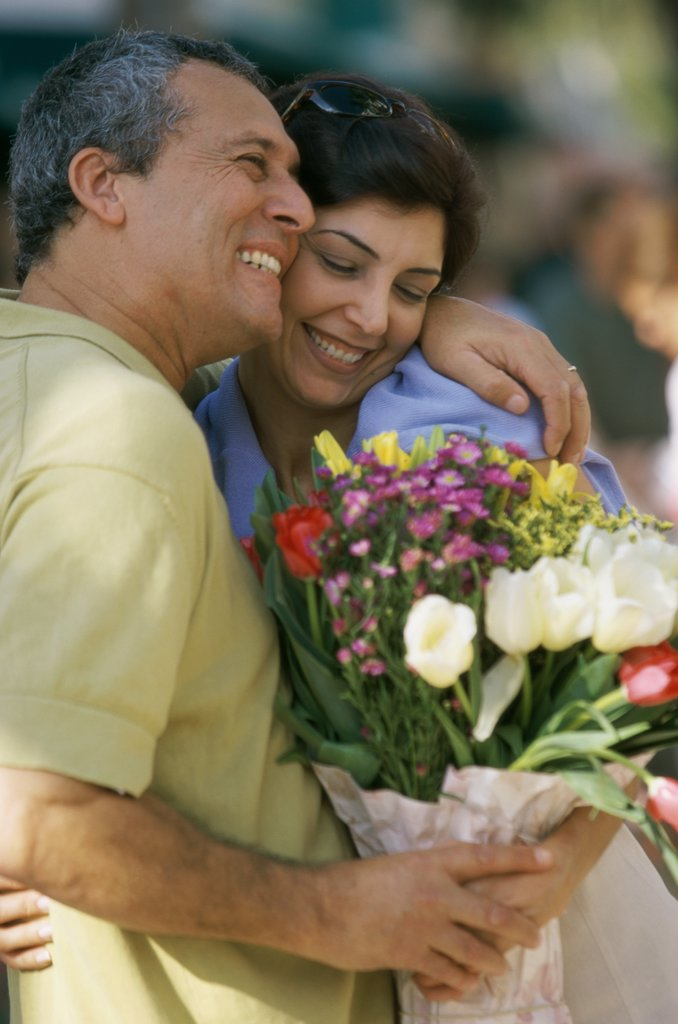 Close-up of a mid adult couple holding a bouquet of flowers : Stock Photo
