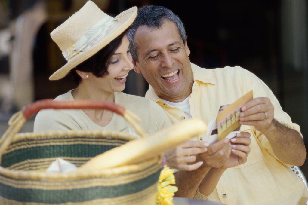 Mature couple choosing postcards : Stock Photo