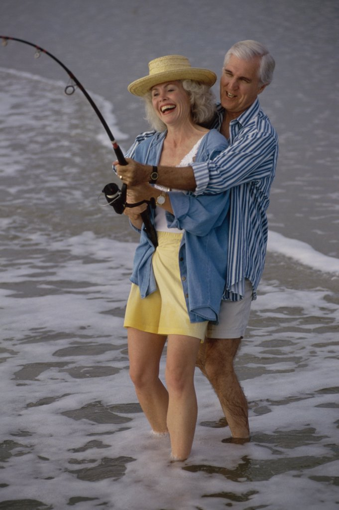 Stock Photo: 1574R-01305A Senior couple fishing together on the beach