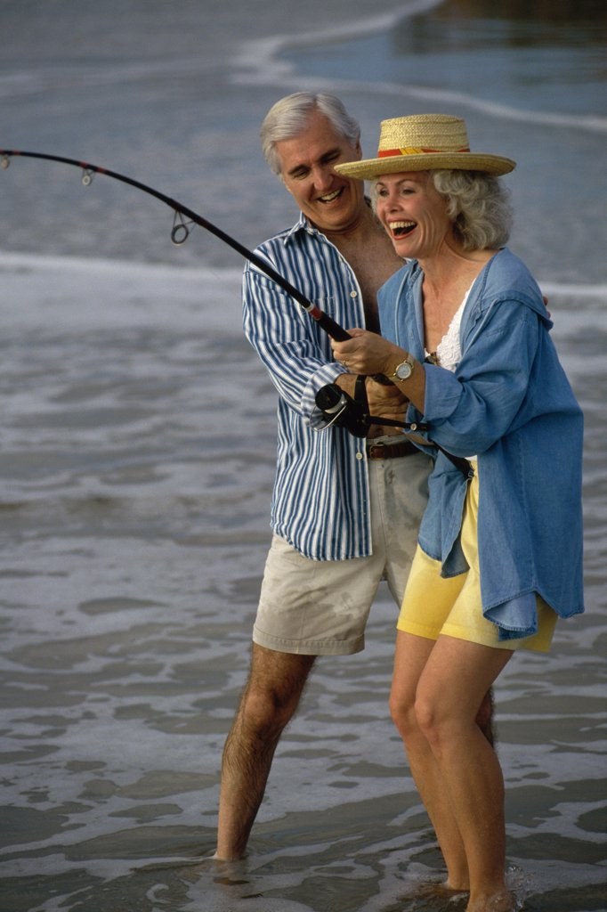 Senior couple fishing together on the beach : Stock Photo