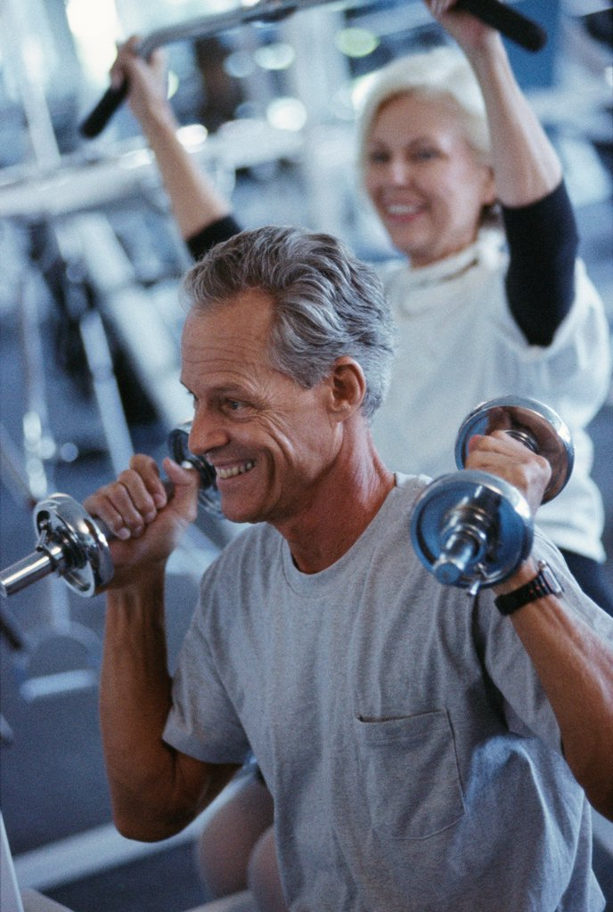 Stock Photo: 1574R-013073 Senior couple exercising in a gym