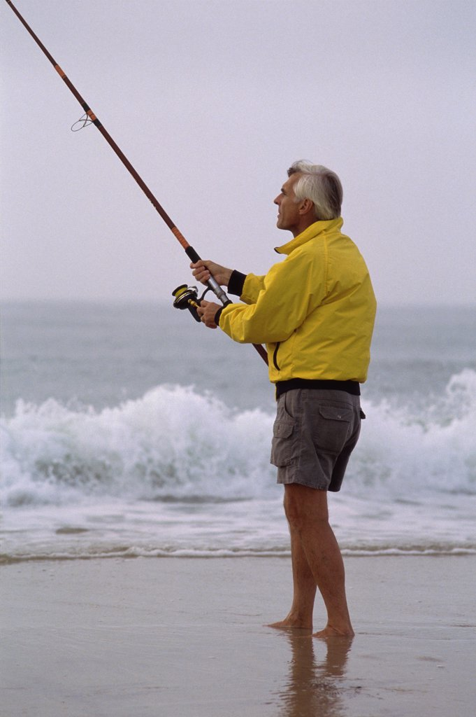 Senior man fishing on the beach : Stock Photo
