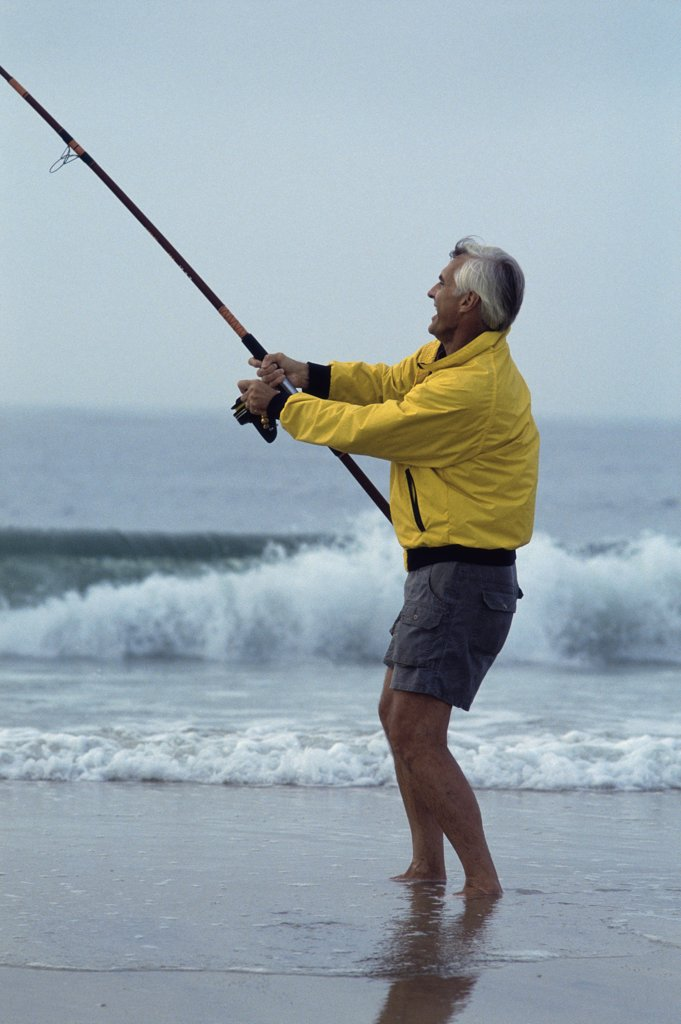 Side profile of a senior man fishing at the beach : Stock Photo