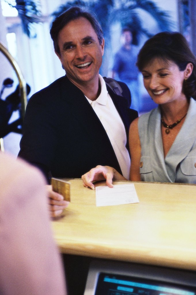 Mature couple making a payment with a credit card at a hotel reception desk : Stock Photo