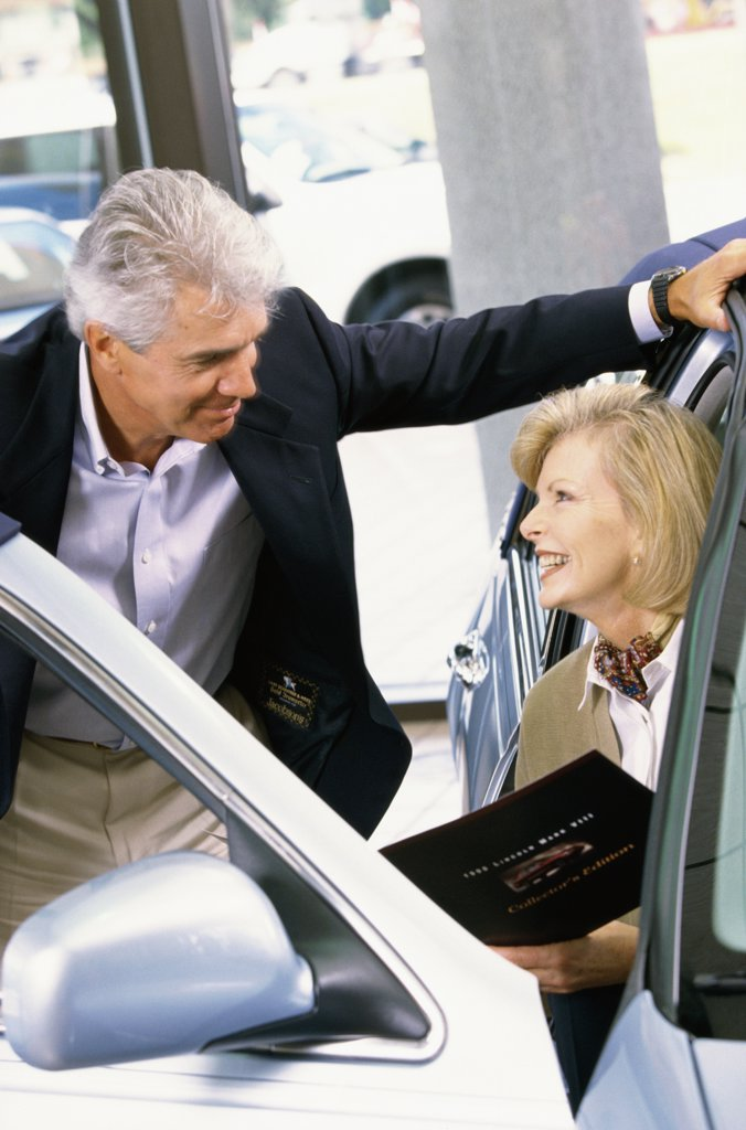 Mature man talking to a mature woman sitting in a car : Stock Photo