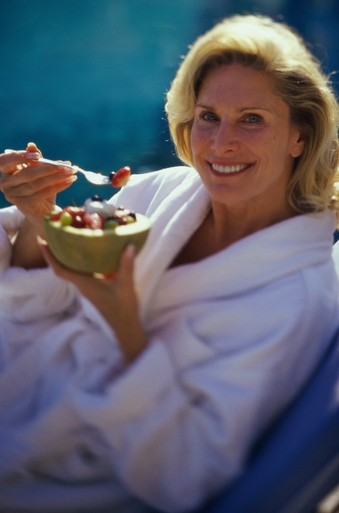 Portrait of a mature woman holding a bowl of fruit salad : Stock Photo