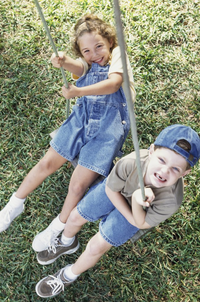 High angle view of a boy and girl swinging on a swing : Stock Photo