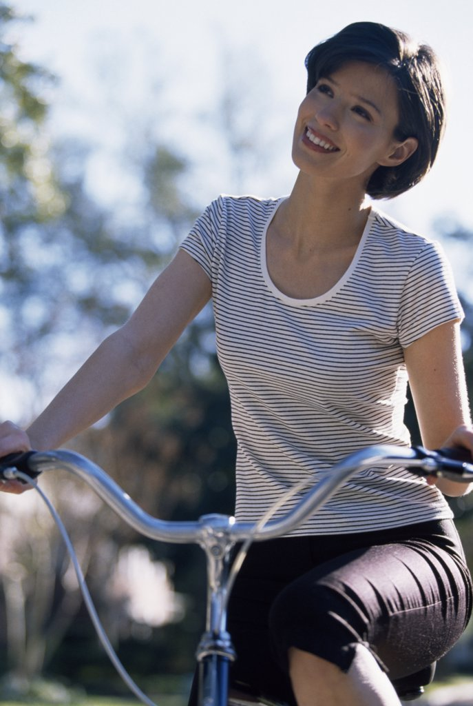 Close-up of a young woman cycling : Stock Photo