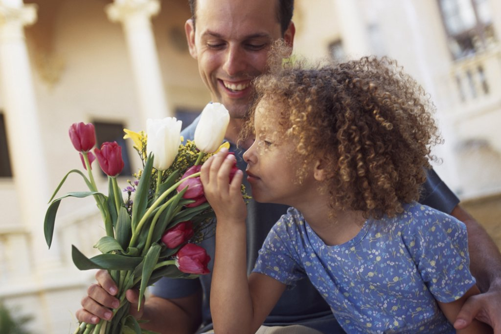 Father holding a bouquet of flowers with his daughter : Stock Photo