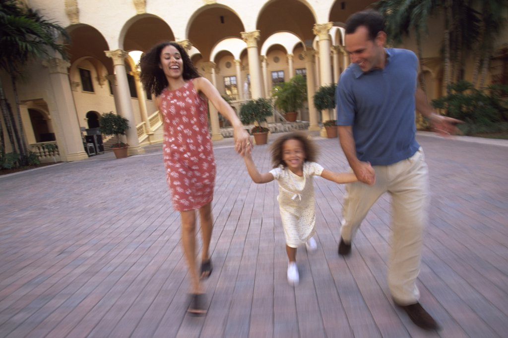 Parents holding hands with their daughter and running : Stock Photo