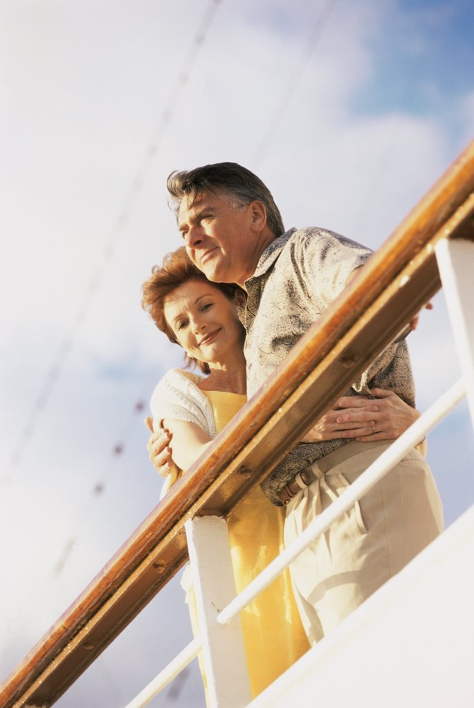 Low angle view of a couple standing against the railing of a ship : Stock Photo
